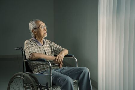 Picture of senior man sits in the wheelchair while thinking something in the retirement home
