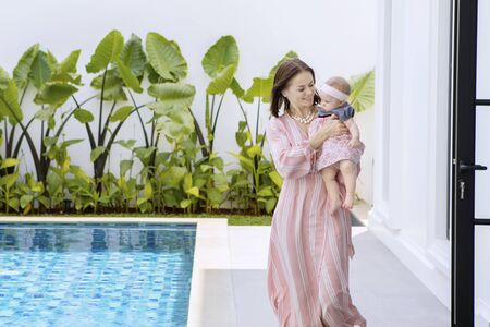 Caucasian woman playing with her baby while standing near the swimming pool
