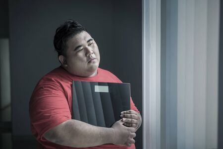 Picture of an obese man looks unhappy while holding a weight scale and standing near the window