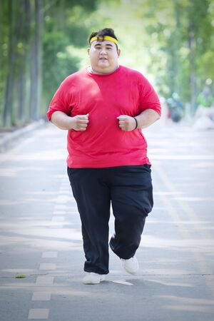 Portrait of an Asian fat man wearing sportswear while doing run exercises in the park