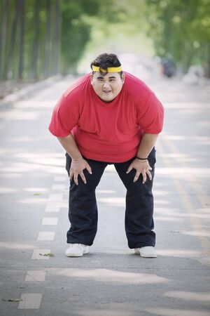 Portrait of obese man catching breath after running in the park