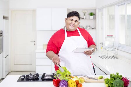 Picture of happy fat man mixing salad in the kitchen while holding a digital tablet