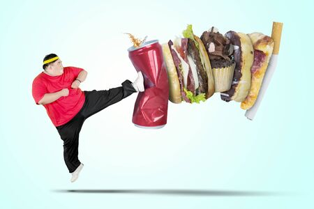 Picture of young fat man wearing sportswear while kicking soft drink and fast food Imagens