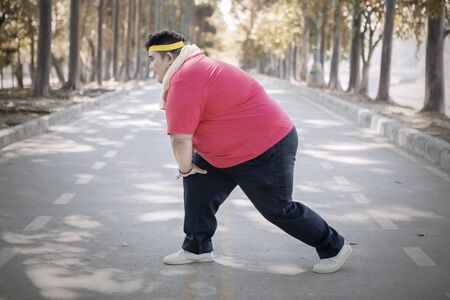 Picture of an obese man stretching his leg before exercising in the park at autumn time