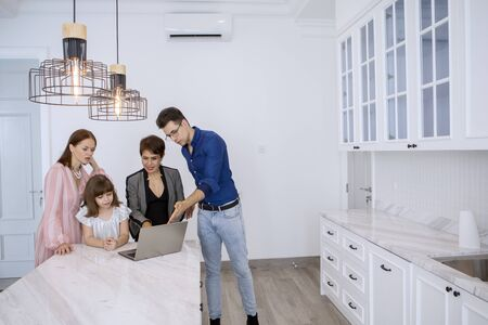 Picture of Caucasian family consulting a new house with their real estate agent