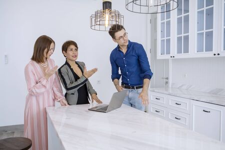 Picture of female real estate agent showing kitchen interior to her customer