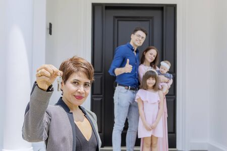Real estate agent handing over keys of new house  while standing with her client