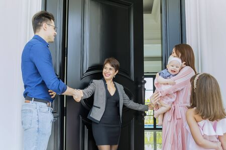 Caucasian family welcomed by their realtor to enter new house while standing near a door
