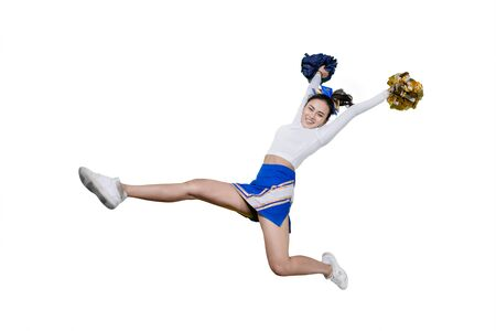Picture of a happy cheerleader girl lifting pom poms while jumping in the studio