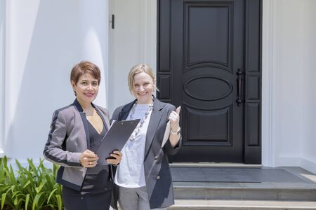 Two saleswoman smiling at the camera while standing outside a house for sale