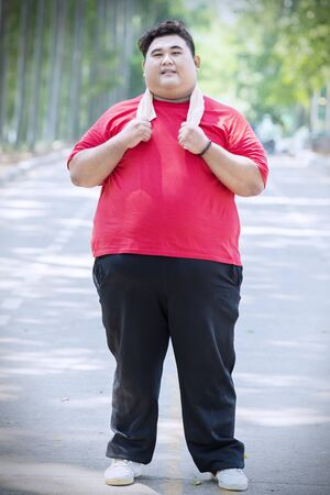 Full length of overweight man wearing sportswear while standing in the park
