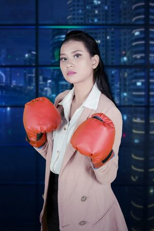 Young businesswoman looks angry while wearing boxing gloves and standing in the office Stock Photo