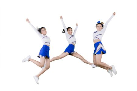 Group of pretty cheerleader girls lifting hands while jumping together in the studio, isolated on white background 写真素材