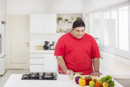 Young fat man holding a knife while preparing healthy salad in the kitchen