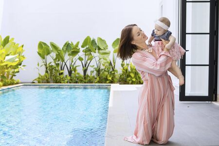 Picture of young woman playing with her baby while sitting near the swimming pool