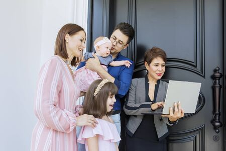 Happy family consulting with their real estate agent while standing together near a door