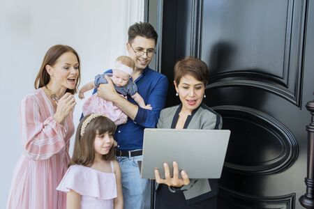 Female realtor using a laptop while explaining house plan to Caucasian family 스톡 콘텐츠