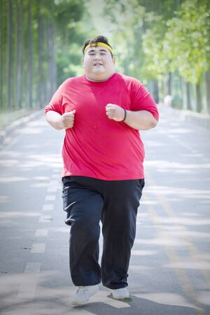 Portrait of happy obese man wearing sportswear while doing run exercises in the park