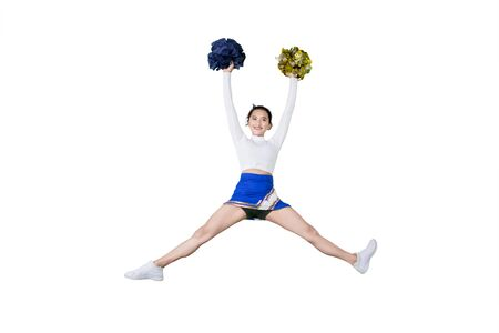 Picture of beautiful cheerleader performing dances with pom poms while jumping in the studio
