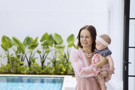 Picture of young woman having fun with her baby while standing near the swim pool 写真素材