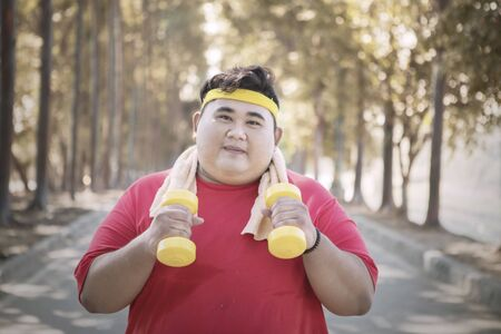 Picture of Asian fat man holding two dumbbells while jogging in the park at autumn time 写真素材