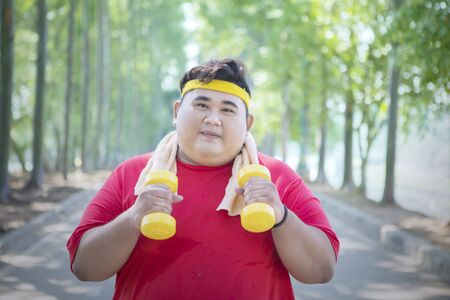 Happy fat man doing run exercise in the park while holding two dumbbells