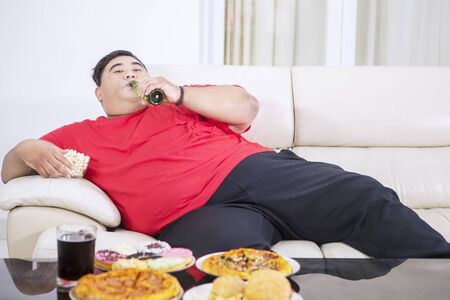 Young fat man eating junk foods and drinking beer while sitting on the sofa and watching TV at home