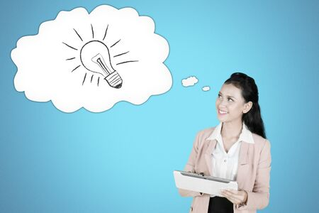 Picture of female entrepreneur using a digital tablet in the studio while looking at a cloud bubble with light bulb