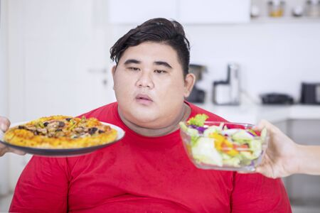 Overweight man does not know what to choose between pizza and salad Stock Photo