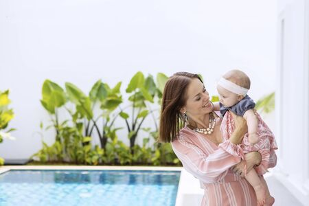 Picture of young mother playing with her baby near the swimming pool