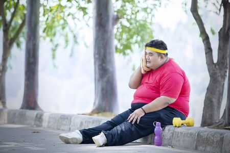 Picture of an overweight man wiping his sweat while resting after exercise in the park