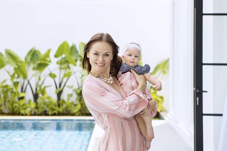 Young woman smiling at the camera while holding her baby and standing near the swimming pool 写真素材