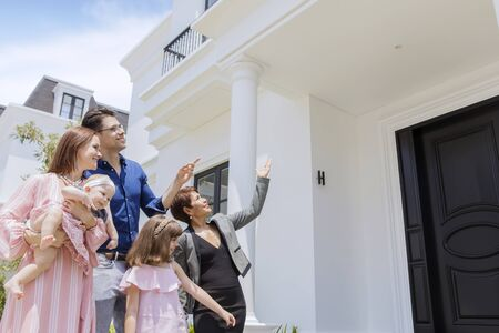Picture of Caucasian family looking at exterior of new house with their realtor