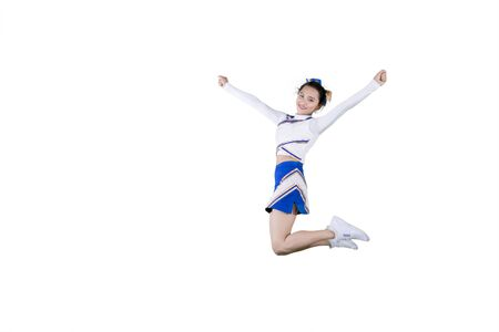 Picture of beautiful cheerleader smiling at the camera while leaping with copy space in the studio, isolated on white background