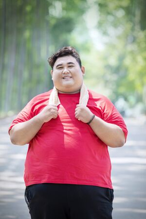 Portrait of happy obese man wearing sportswear while standing in the park
