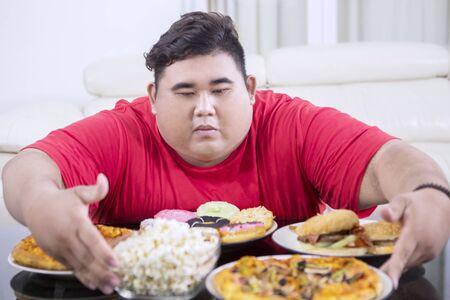 Picture of a greedy fat man hugging at a lot of unhealthy food on the table. Shot at home