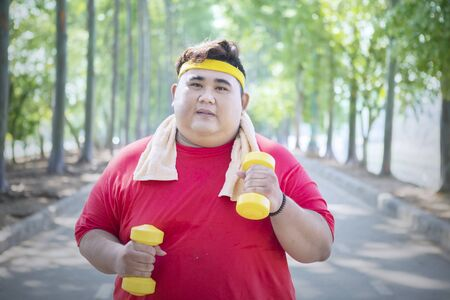 Picture of an overweight man jogging in the park while holding two dumbbells