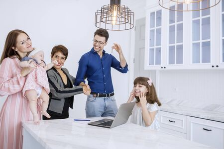 Picture of Caucasian family showing house keys while handshaking with their real estate agent
