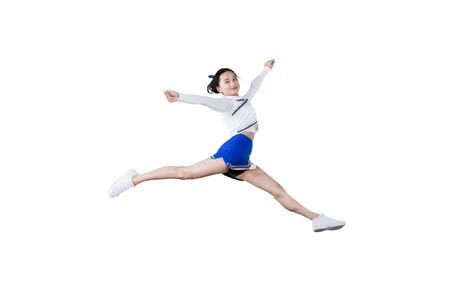 Young female cheerleader smiling at the camera while jumping in the studio, isolated on white background