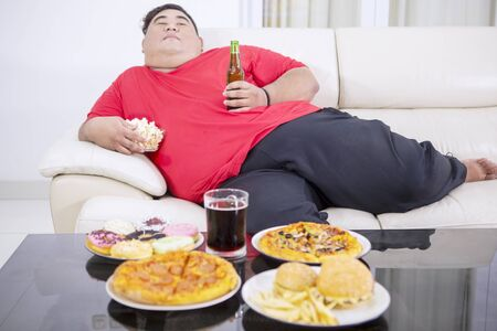 Overweight man eating junk foods and drinking beer while sitting on the sofa and watching TV at home