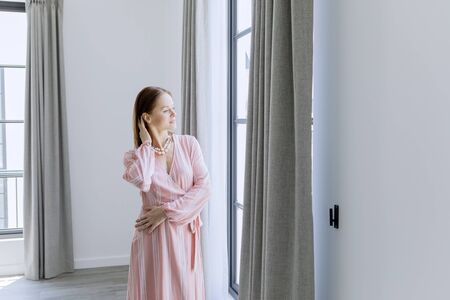 Picture of beautiful woman looks pensive while looking out the window in the new house Stock Photo