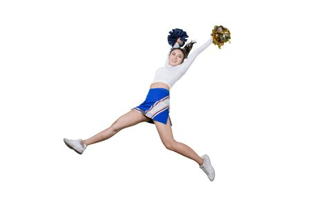 Picture of a pretty cheerleader lifting pom poms while jumping in the studio Stock Photo