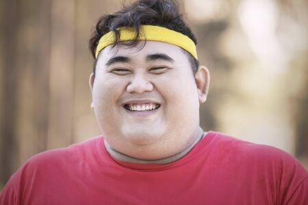 Close up of young fat man smiling at the camera while wearing sportswear in the park at autumn time