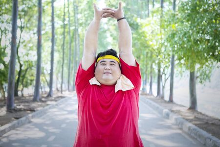 Image of overweight man looking at the camera while doing stretch exercises on the road