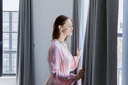 Picture of a beautiful Caucasian woman opening curtains while looking out the window in the new house Stock Photo