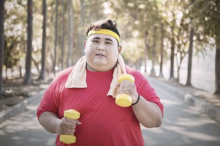 Young obese man holding two dumbbells while jogging in the park at autumn time