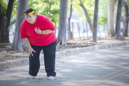 Picture of young obese man having heart pain after running in the park while standing on the road 版權商用圖片