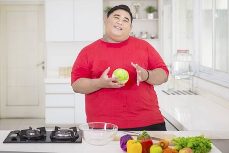 Picture of obese man holding a cabbage while preparing to make a tasty salad in the kitchen Stock Photo