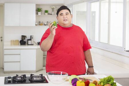 Picture of an overweight man holding a green paprika while preparing to make a tasty salad in the kitchen Stock Photo