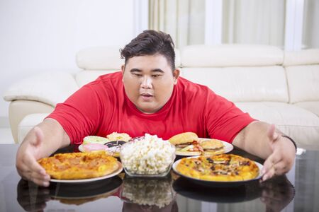 Picture of a young obese man embracing lots of unhealthy food on the table. Shot at home